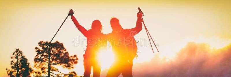 Aktiva utomhus- livsstilparfotvandrare som hurrar framgång som uppnår deras överkant för berg för affärsföretagmål trekking med a fotografering för bildbyråer