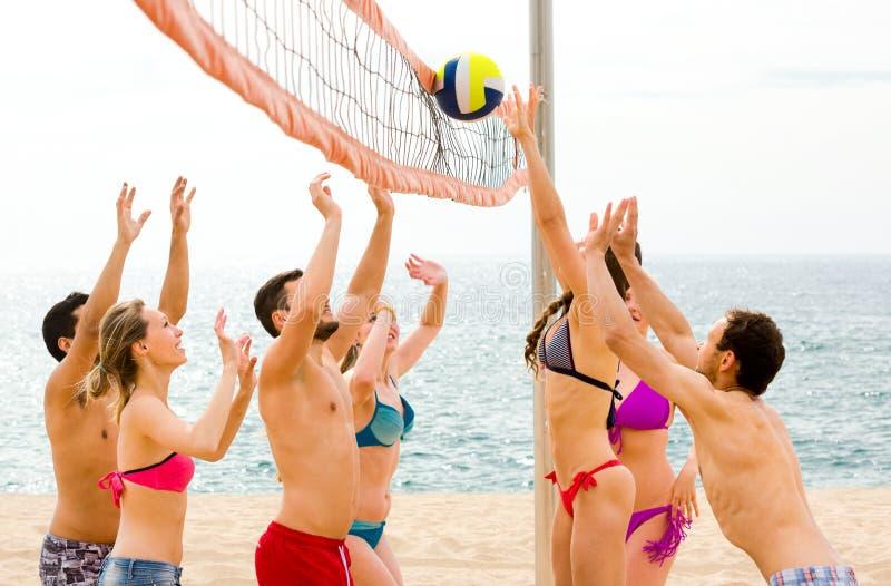 Aktiva vuxna människor som spelar beachvolley arkivfoton