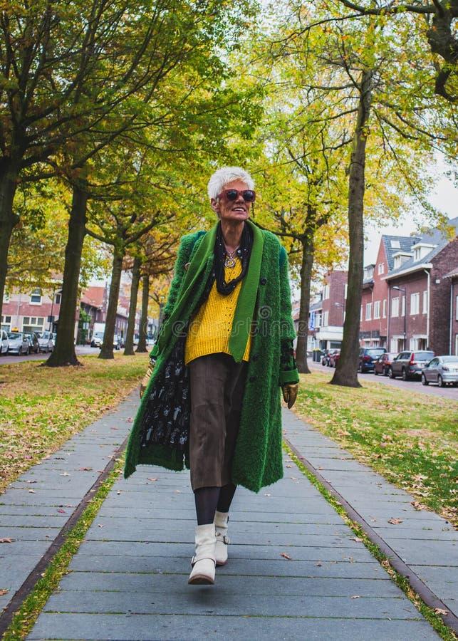 Aktive ältere Dame siebzig Jährige in der bunten Kleidung und in der Sonnenbrille, die in eine alte niederländische Stadt lächelt lizenzfreie stockfotos