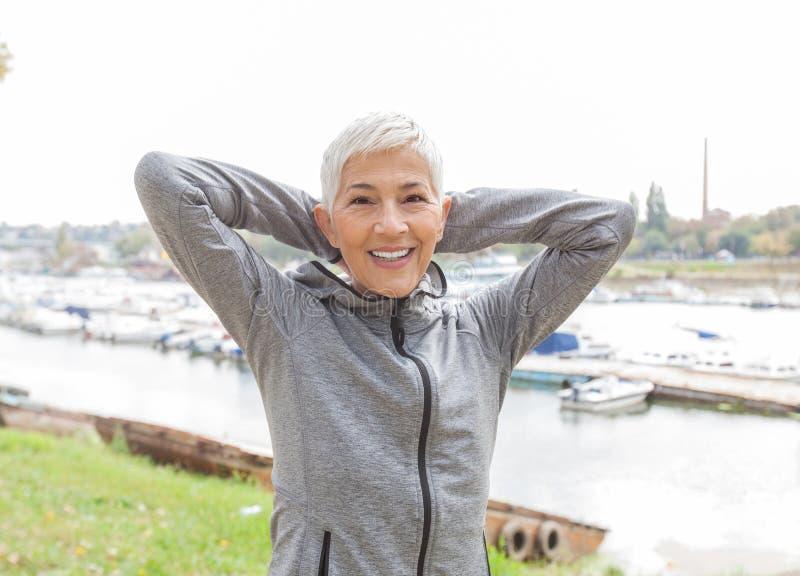 Aktive ältere Frau, die Eignungs-Übung tut stockfotos
