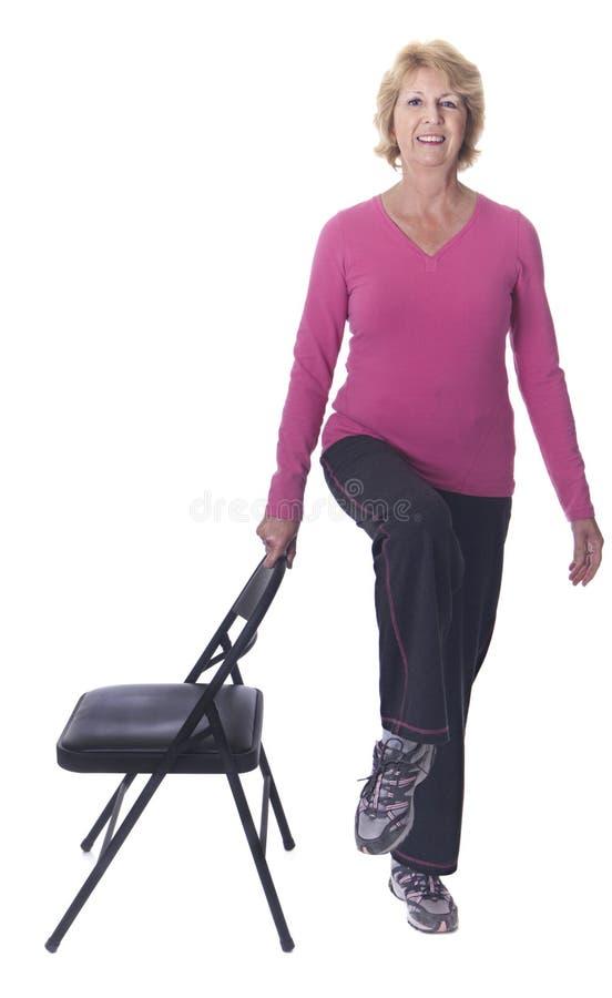 Aktive ältere Frau, die Stuhlübung tut lizenzfreie stockfotografie