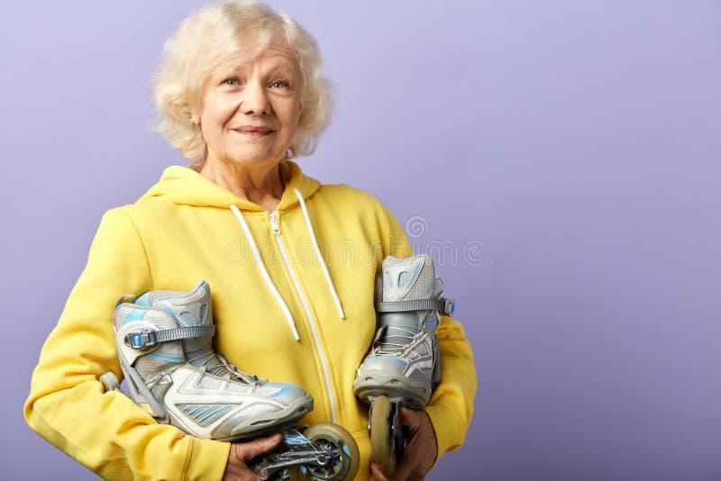Aktive ?ltere Frau im gelben Sport Hoodiehalten l?uft zuhause aufwerfen Rollschuh stockfotografie