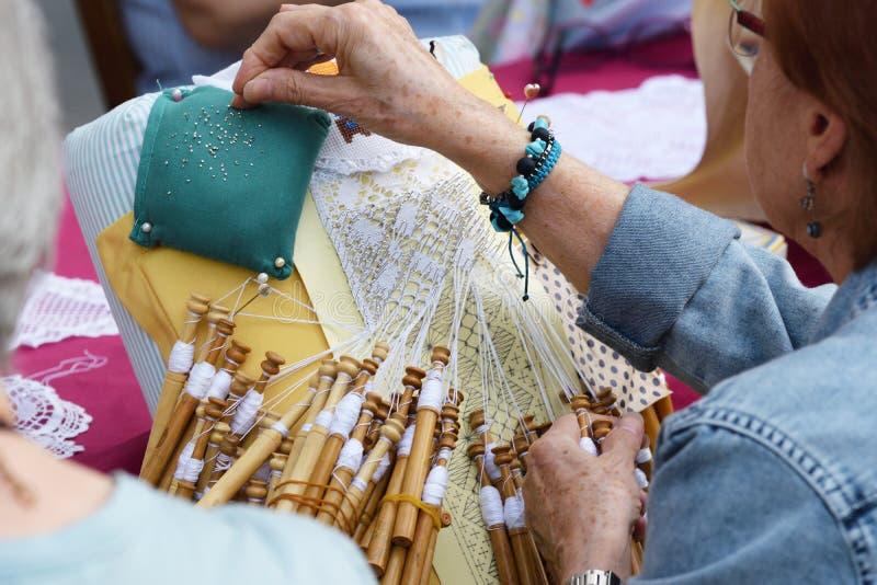 Aktive ältere Leutewerkstatt mit traditioneller Klöppelspitzehäkelarbeit Hände führen einzeln auf und leeren Kopienraum lizenzfreie stockfotos