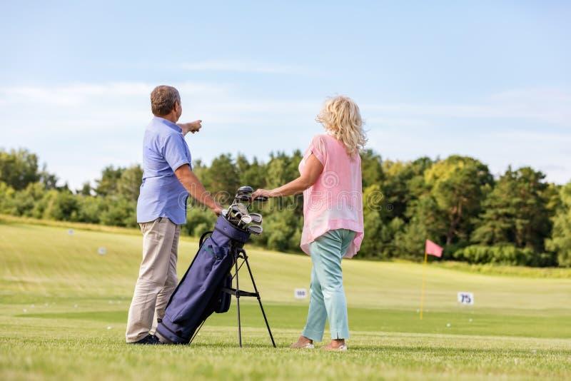 Aktive ältere Paare, die Golf auf einem Kurs spielen stockfoto