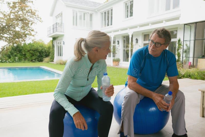 Aktive ältere Paare, die zu Hause mit einander nach Training im Portal sprechen stockfoto