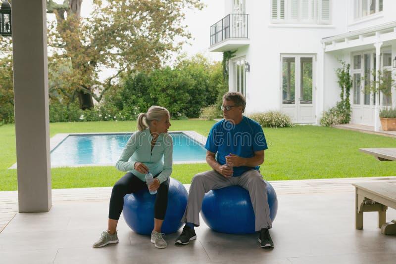 Aktive ältere Paare, die zu Hause mit einander nach Training im Portal sprechen stockbilder