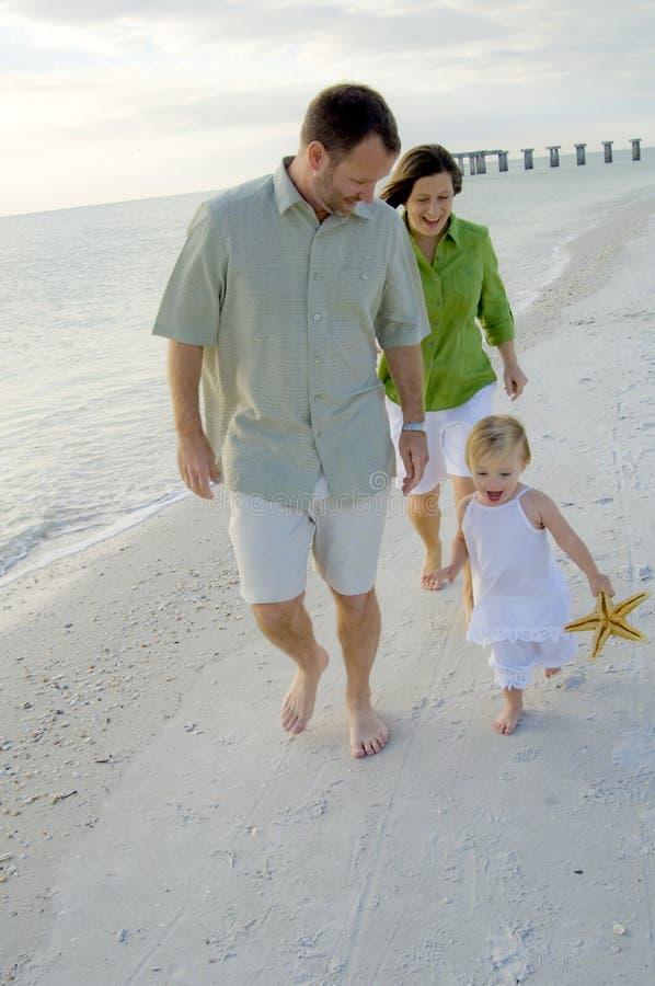 Aktive Familie, die auf Strand spielt stockfotografie