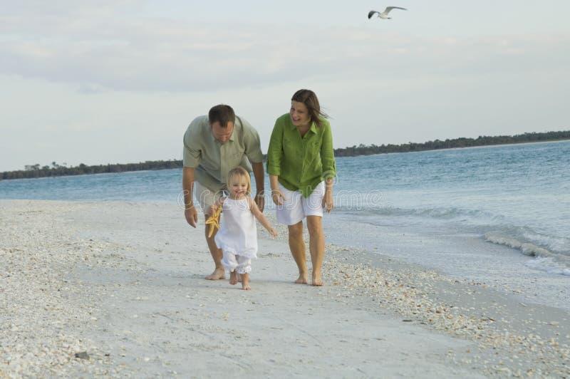 Aktive Familie, die auf Strand spielt stockfotos