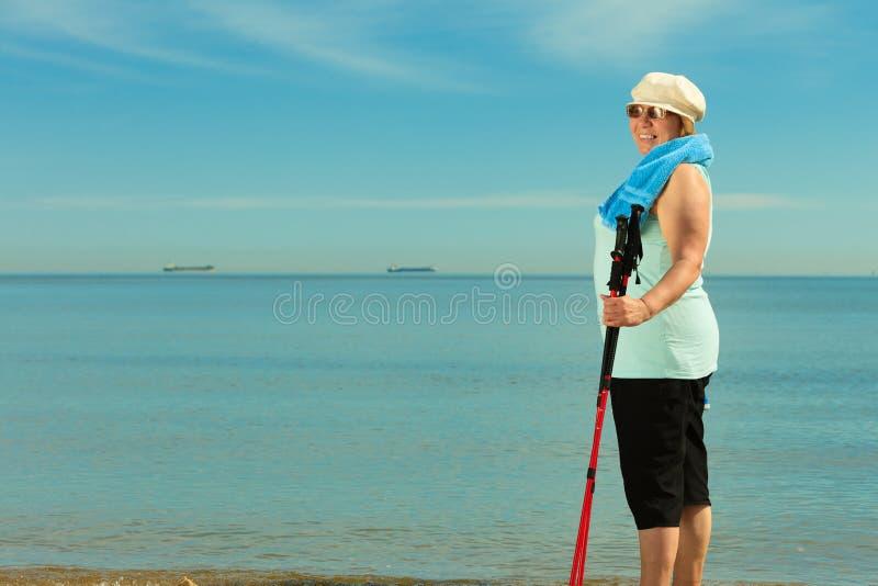 Aktive Frau älterer Nordic, der auf einen Strand geht lizenzfreie stockbilder
