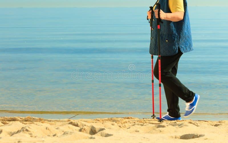 Aktive Frau älterer Nordic, der auf einen Strand geht fahrwerkbeine lizenzfreie stockbilder