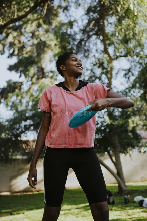 Aktive Frau, die einen Frisbee im Park wirft lizenzfreies stockbild