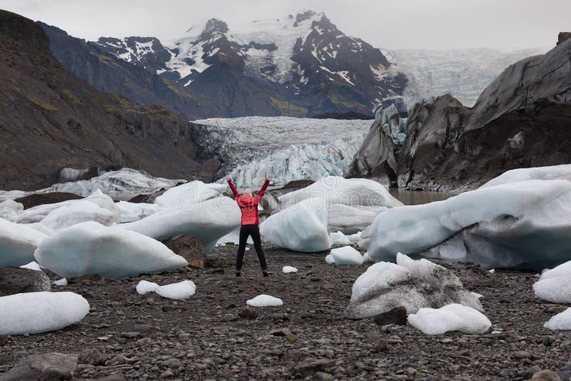 Aktive Frau, die in hellen roten Regenmantel nahe der Gletscher-Lagune springt stockfoto