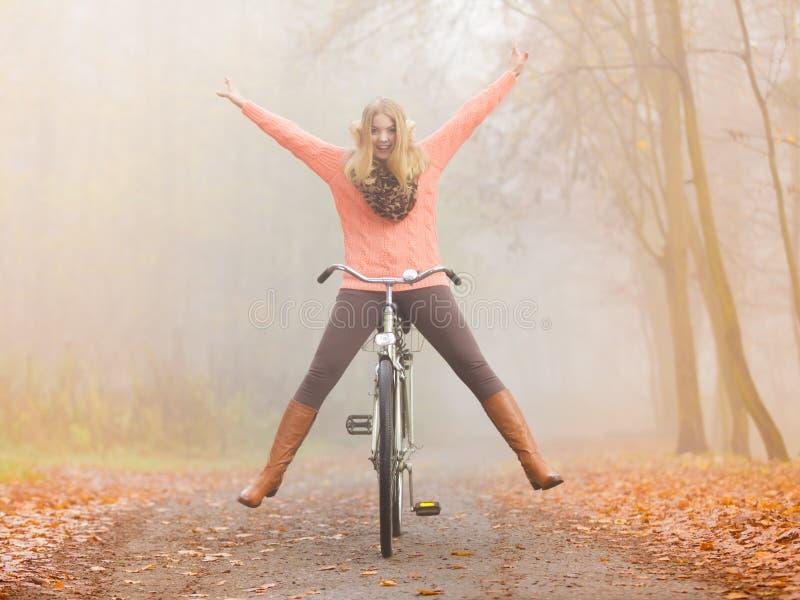 Aktive Frau, die Spaßreitfahrrad im Herbstpark hat stockbild