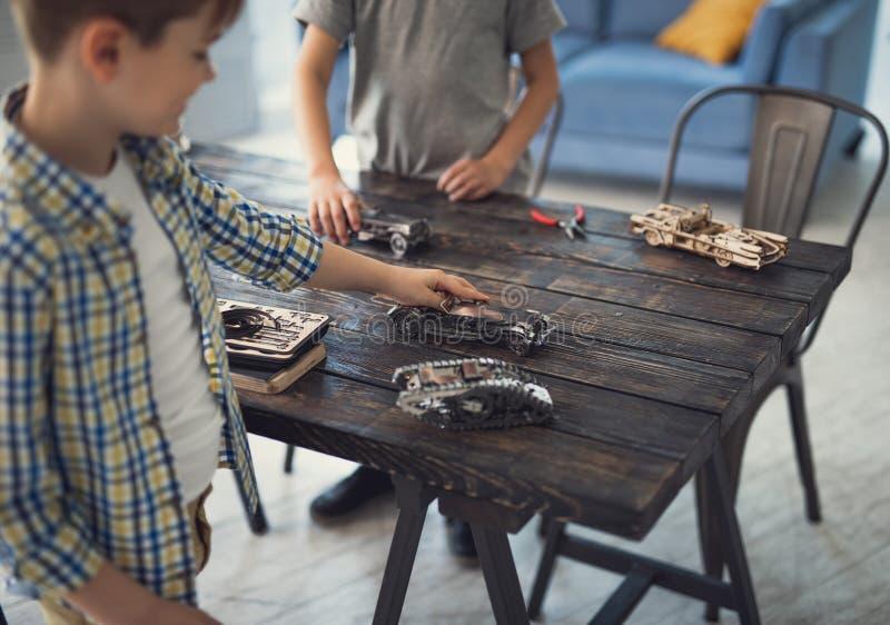 Aktive Jungen, die auf dem Tisch Rennen beim Sein zu Hause organisieren lizenzfreies stockfoto