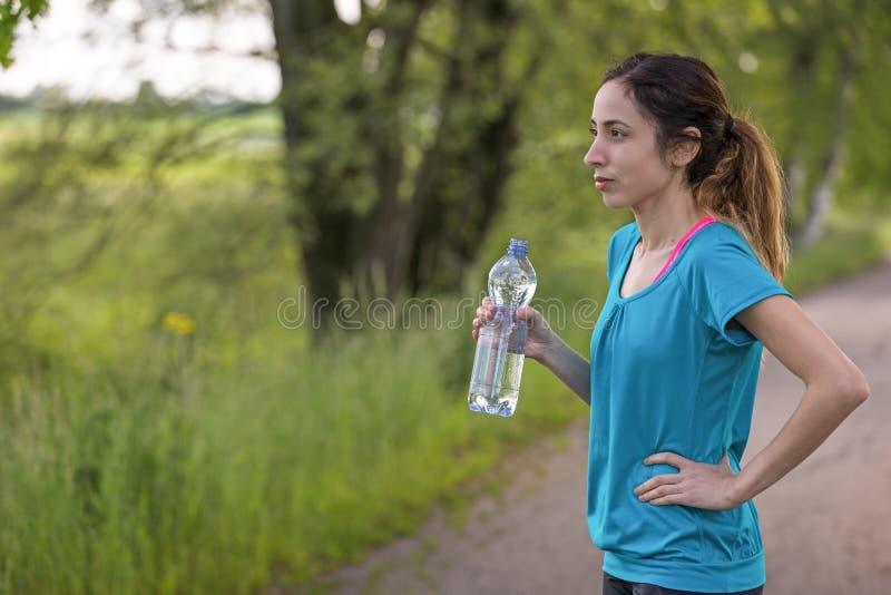 Aktive Läuferfrau mit einer Flasche Wasser in ihrer Hand i im Freien stockbild