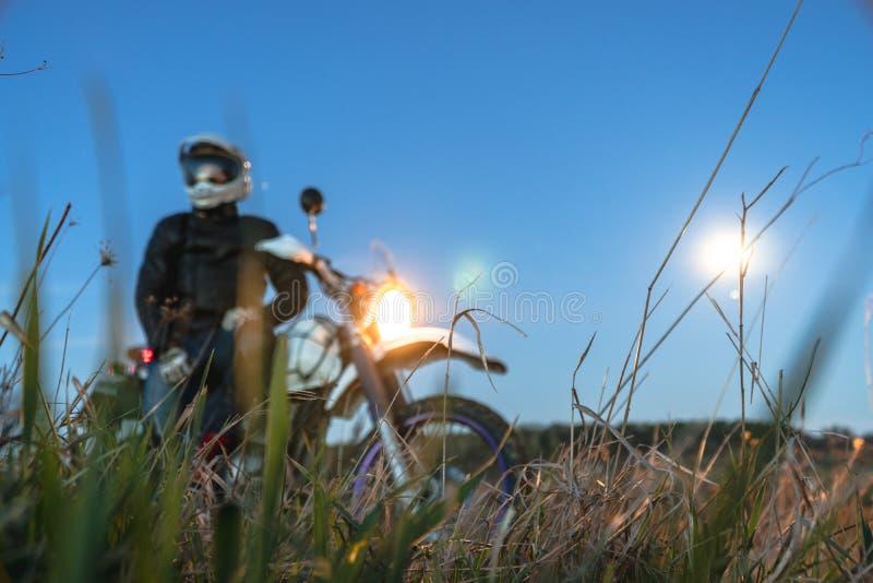 Aktive Lebensart, enduro Motorrad, ein Kerl betrachtet die Sterne nachts und den Mond, Einheit mit Natur, der Geist des Abenteuer lizenzfreie stockfotos