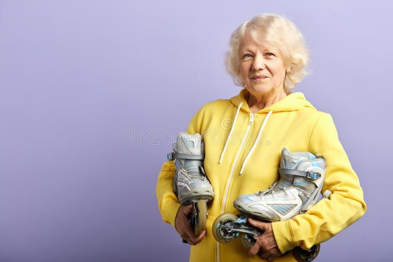 Aktive ?ltere Frau im gelben Sport Hoodiehalten l?uft zuhause aufwerfen Rollschuh stockfoto