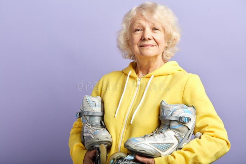 Aktive ?ltere Frau im gelben Sport Hoodiehalten l?uft zuhause aufwerfen Rollschuh lizenzfreies stockfoto
