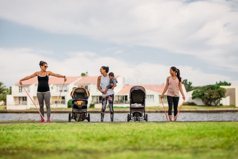 Aktive Mütter im Park mit ihren Kindern früh morgens stockfotografie