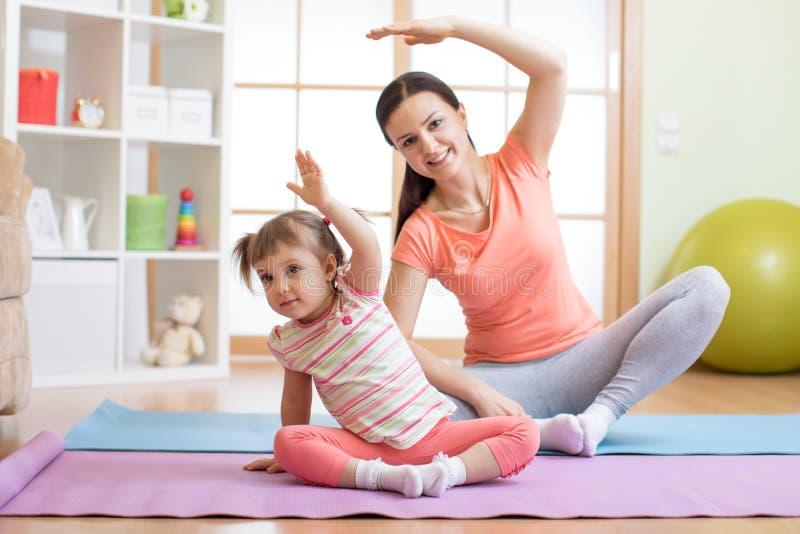 Aktive Mutter- und Kindertochter nehmen an Eignung, Yoga, trainieren zu Hause teil lizenzfreies stockfoto