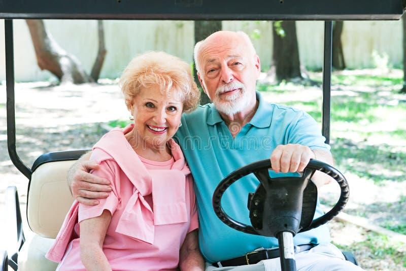 Aktive Senioren im Golfmobil lizenzfreie stockfotos