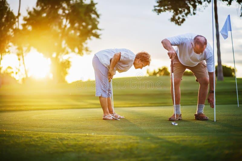 Aktiver älterer Lebensstil, älteres Paar, das zusammen Golf bei Sonnenuntergang spielt stockbild