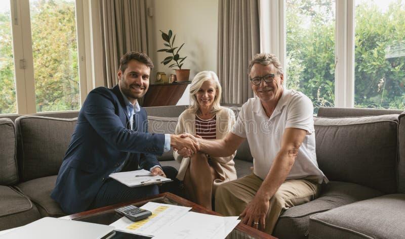 Aktiver älterer Mann, der Hände mit Immobilienagentur im Wohnzimmer rüttelt stockbilder