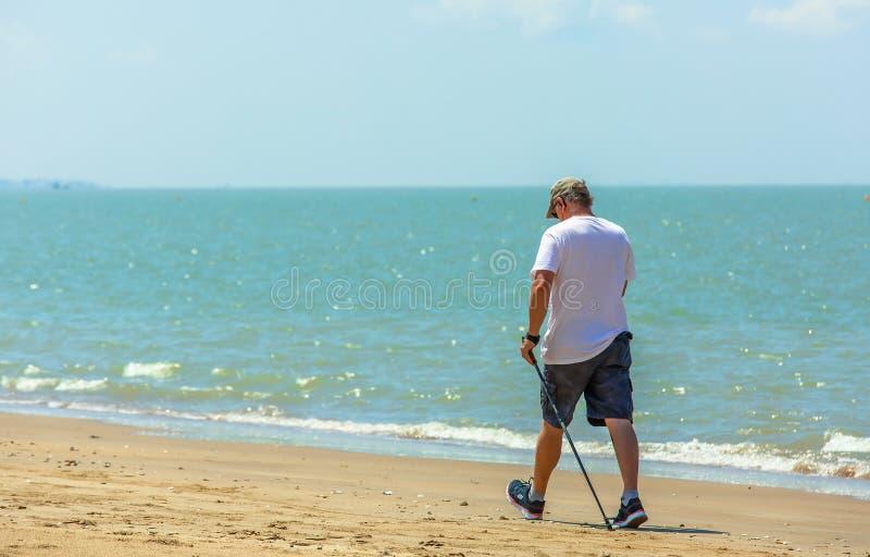 Aktiver älterer Mann, der mit nordischen Wanderstöcken auf dem Strand geht lizenzfreie stockfotografie