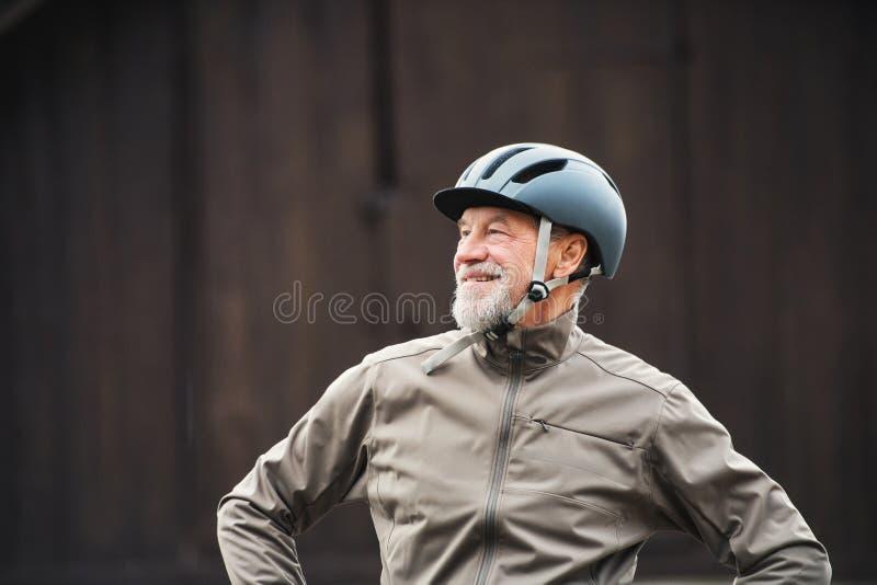 Aktiver älterer Mann mit dem Fahrradsturzhelm, der draußen againts dunklen Hintergrund steht stockfotografie