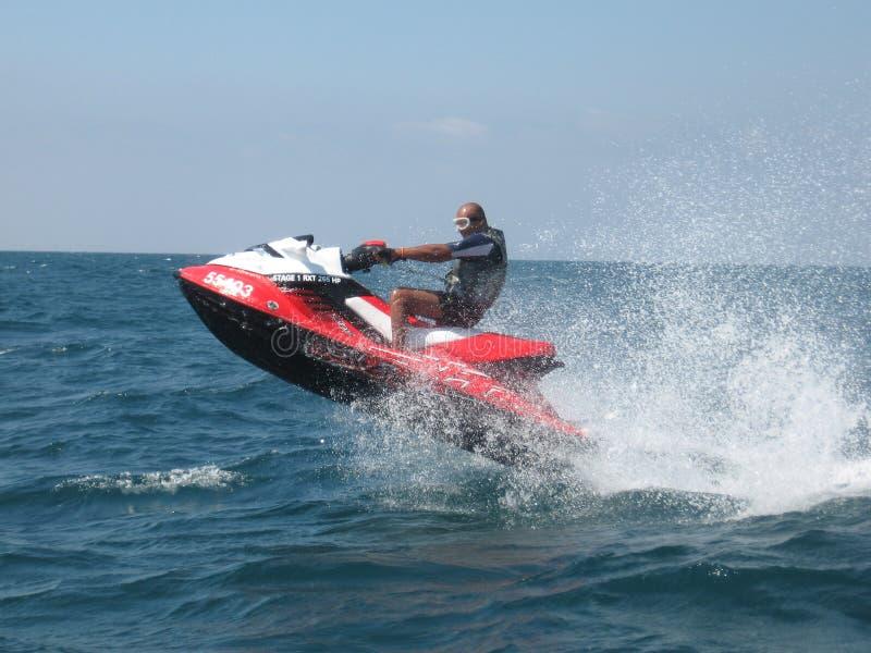 Aktiver Mann, der einen roten Jet-Ski im Roten Meer reitet stockfotografie