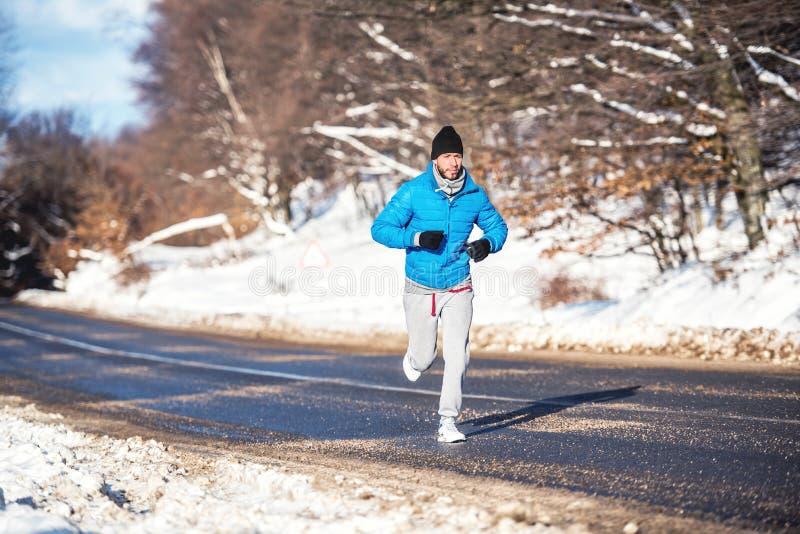 Aktiver Mann, rüttelnd und laufen während eines sonnigen Wintertages Ausarbeiten im Freien stockbilder