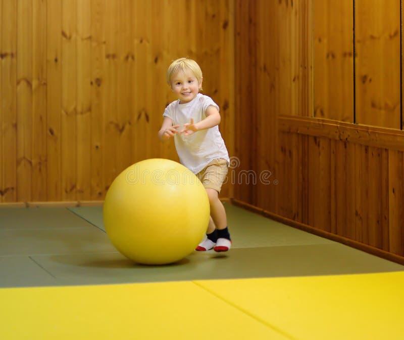 Aktiver Vorschuljunge, der mit großem Ball in der Innensporthalle/im Sportunterricht spielt lizenzfreie stockfotografie