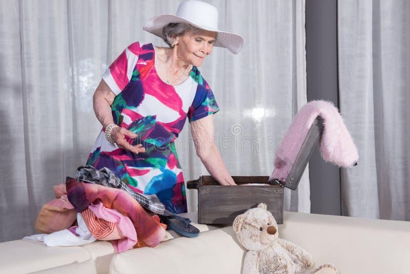 Aktiver weiblicher Senior verpackt Weinlesekoffer für Sommerferien stockfotografie