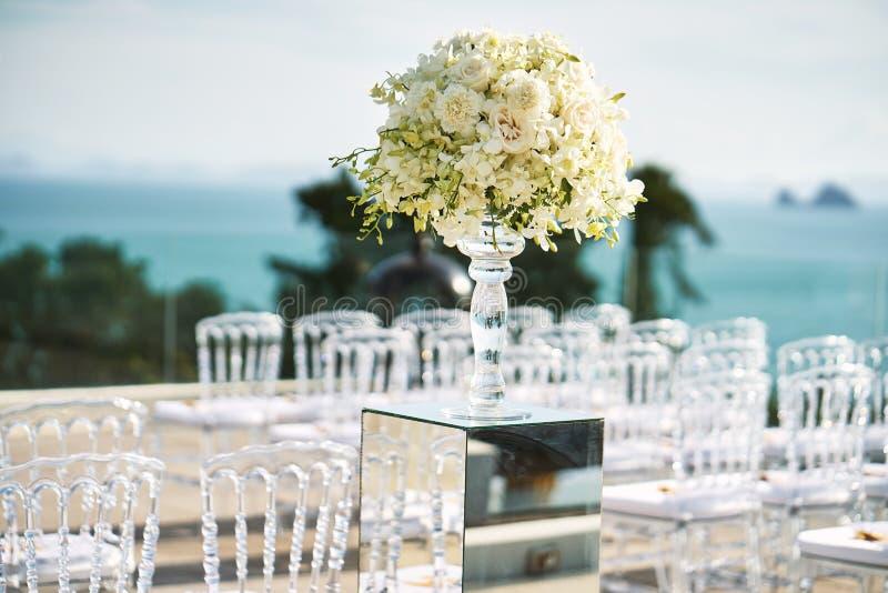 Aktiveringen för mötesplatsen för strandbröllop med vit blomman för den rosor och på spegeln boxas vasgarnering arkivbilder