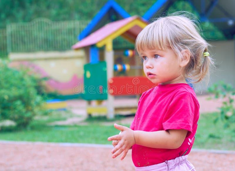 Aktives kleines kaukasisches Mädchen in einem roten T-Shirt und mit Endstücken auf Spielplatz - Nahaufnahmeschuß stockbild