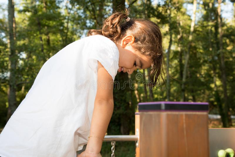 Aktives kleines Mädchen auf Spielplatz für Kind im Stadtpark stockbild