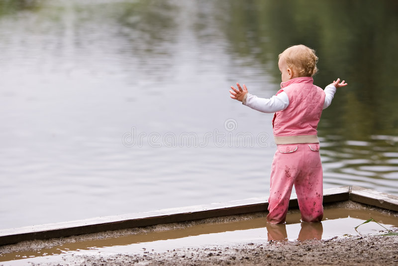 Aktives Kleinkind in der Pfütze lizenzfreie stockfotos