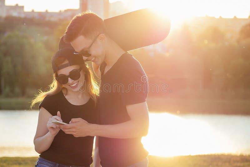 Aktives Sportsklimmen im Sommerpark schöne Frau und Mann haben Spaß mit Skateboard-Langboard Hintergrund lizenzfreie stockbilder