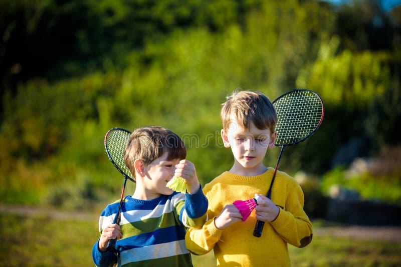 Aktives Vorschulmädchen und Junge, die Badminton Gericht im im Freien im Sommer spielt Kinderspieltennis Schulsport für Kinder Sc stockfotos