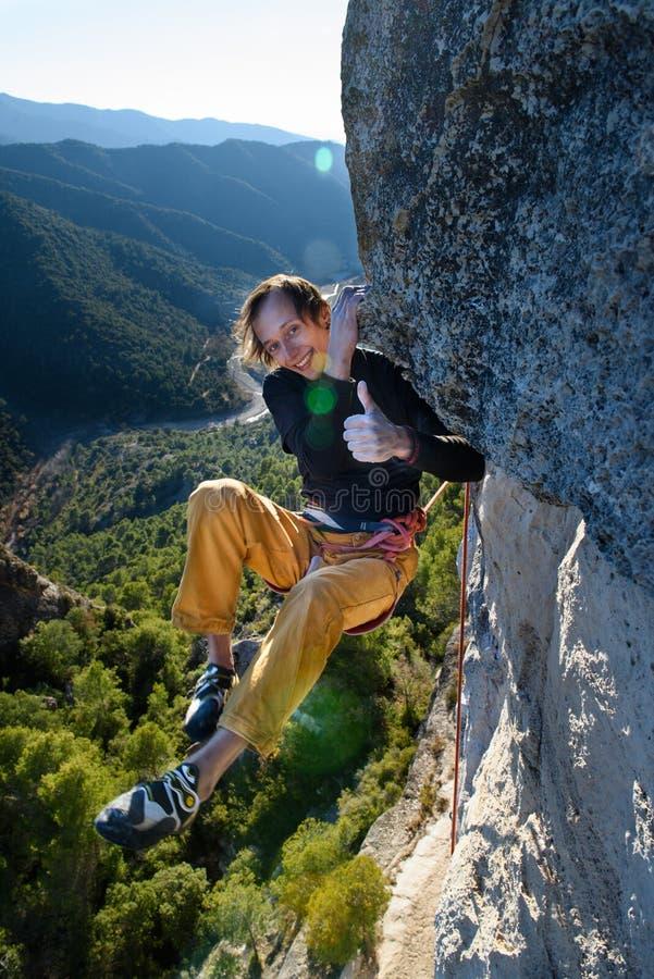 Aktivitet för utomhus- sport Lyckligt vagga klättraren som stiger en utmanande klippa Extrem sportklättring royaltyfria bilder