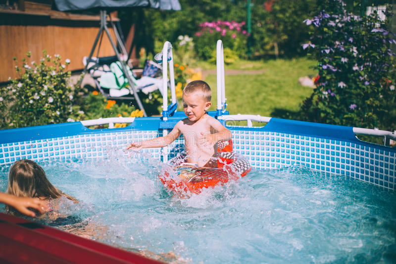 Aktiviteter på pölen, barn som simmar och spelar i vatten arkivfoto
