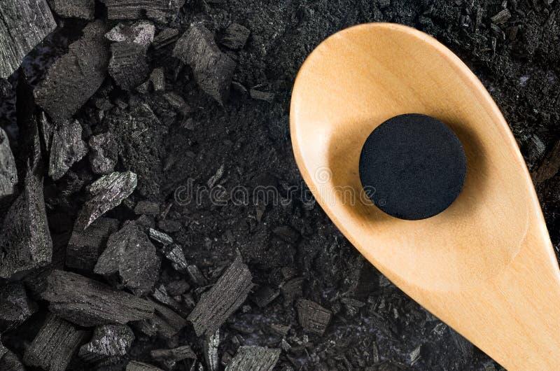 Aktivkohlepillenmedizin im hölzernen Löffel auf Boden Holzkohle stockbilder