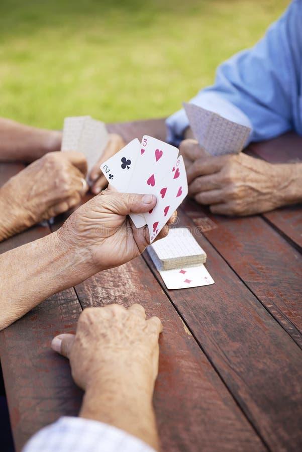Aktivpensionärer, grupp av gammal vän som leker kort på, parkerar arkivbild