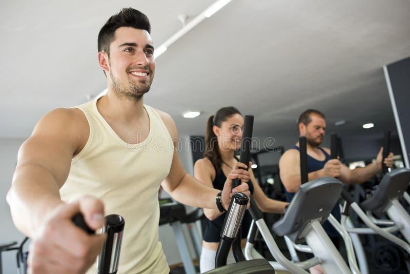Aktivt folk på idrottshallen i ellipsformig cykel royaltyfria bilder