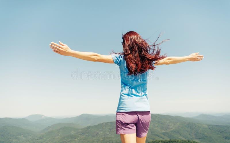 Aktivt kvinnaanseende med lyftta armar i berg royaltyfri foto
