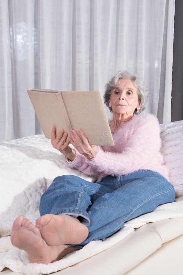 Aktivt kvinnligt högt koppla av på soffan arkivfoto