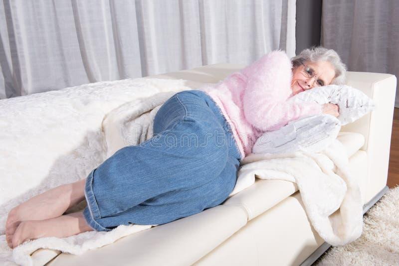 Aktivt kvinnligt högt koppla av på soffan arkivfoton