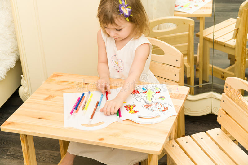 Aktivt litet förskole- ålderbarn, gullig litet barnflicka med blont lockigt hår som drar bilden på att använda för papper som är  arkivfoton