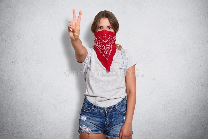 Aktivt säkert kvinnaanseende över grå bakgrund i studio och att lyfta armen och att göra gest och att visa fredtecknet som täcker arkivbild