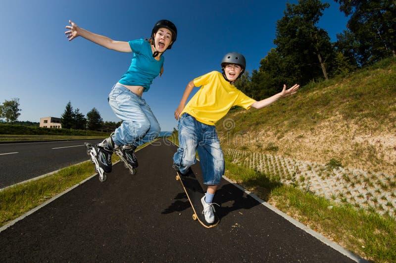 Aktivungdomar - rollerblading som skateboarding royaltyfri fotografi